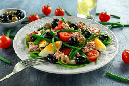 Fresh Tuna Green Bean salad with eggs, tomatoes, beans, olives on white plate. concept healthy food