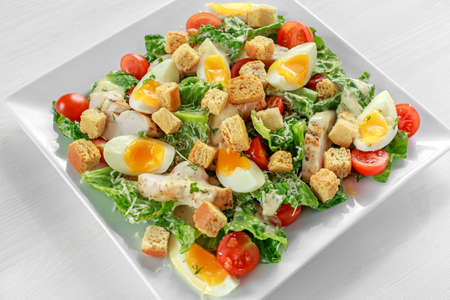 Fresh healthy Caesar salad with chicken, eggs, tomatoes, Cheese and Croutons on white plate