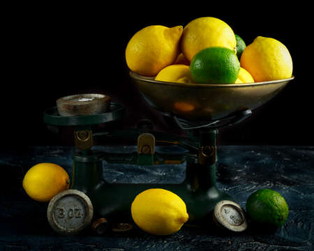 Lemons and limes on vintage old fashion pound scales