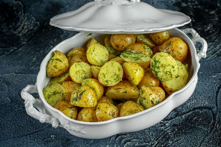 New boiled potatoes with dill and butter in vintage casserole Stock Photo