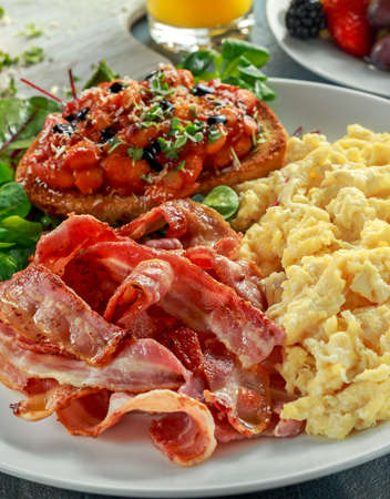 scrambled: Morning Scrambled egg, bacon breakfast with beans in tomato sauce on toasted bread on white plate.