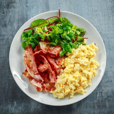 朝スクランブル卵、白い皿にベーコン朝食 写真素材