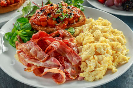 Morning Scrambled egg, bacon breakfast with beans in tomato sauce on toasted bread on white plate Stock Photo