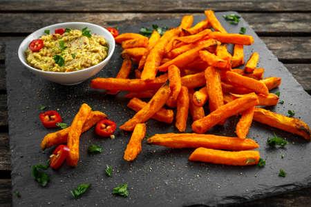 Healthy Homemade Baked Orange Sweet Potato Fries with guacamole, salt, pepper on stine, stone board 스톡 콘텐츠