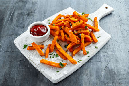 Healthy Homemade Baked Orange Sweet Potato Fries with ketchup, salt, pepper on white wooden board 免版税图像