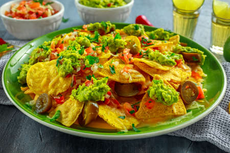 Nachos with cheese, jalapeno peppers, red onion, parsley, tomato, salsa, guacamole sauce and tequila on green plate.