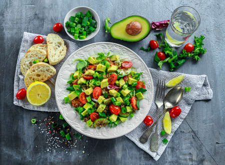 Quinoa tabbouleh salad with avocado, tomatoes, cucumber, green onion. Concept healthy food.