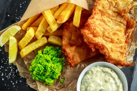 British Traditional Fish and chips with mashed peas, tartar sauce on crumpled paper. Фото со стока