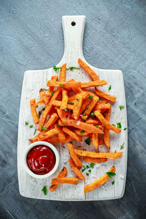 Healthy Homemade Baked Orange Sweet Potato Fries with ketchup, salt, pepper on white wooden board Standard-Bild