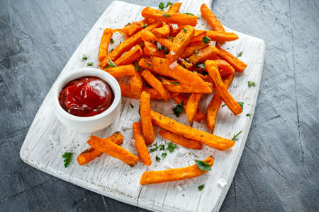 Healthy Homemade Baked Orange Sweet Potato Fries with ketchup, salt, pepper on white wooden board.