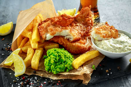 british cuisine: British Traditional Fish and chips with mashed peas, tartar sauce on crumpled paper with cold beer. Stock Photo