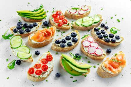 Zelfgemaakte zomer toast met roomkaas gerookte zalm, bosbessen, radijs, komkommer, avocado en waterkers salade. Verse gezonde voeding concept. Stockfoto - 75107126