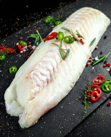 whitefish: Fresh Raw Cod loin fillet with rosemary, chillies, cracked pepper and lemon on stone board Stock Photo