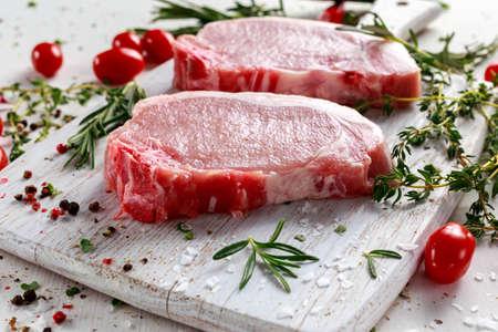 Ruwe varkenslende karbonades op een snijplank met kruiden, rozemarijn, tijm, chili, zout, peper op witte snijplank.