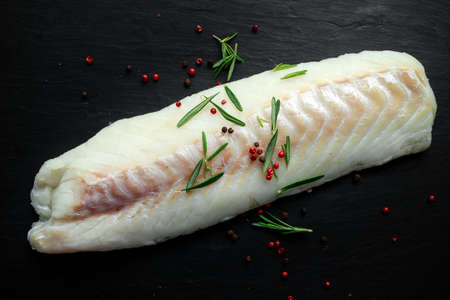 Fresh Raw Cod loin fillet with rosemary, cracked pepper on stone board