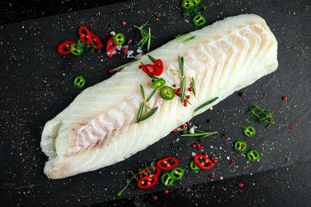 Verse rauwe kabeljauw lendefilet met rozemarijn, pepers, gekraakte paprika op stenen bord Stockfoto