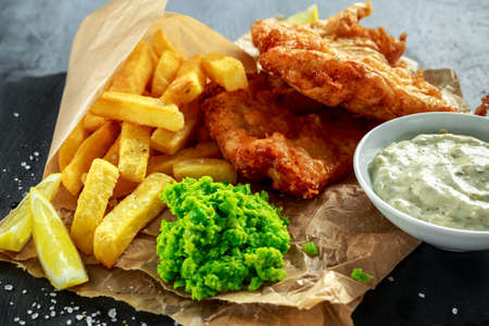 British Traditional Fish and chips with mashed peas, tartar sauce on crumpled paper. Stok Fotoğraf