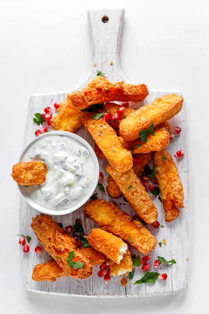 Crispy Halloumi cheese sticks Fries with yogurt for dipping and pomegranate seeds. Stock Photo