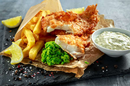 British Traditional Fish and chips with mashed peas, tartar sauce on crumpled paper. Stockfoto