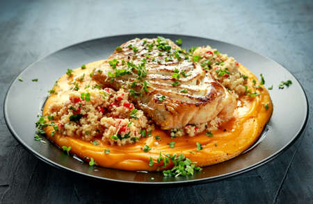 Soy-glazed cod loin fillet with cous-cous salad on butternut squash puree Stock Photo