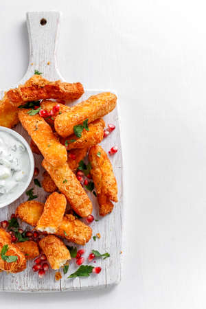 haloumi: Crispy Halloumi cheese sticks Fries with yogurt for dipping and pomegranate seeds. Stock Photo