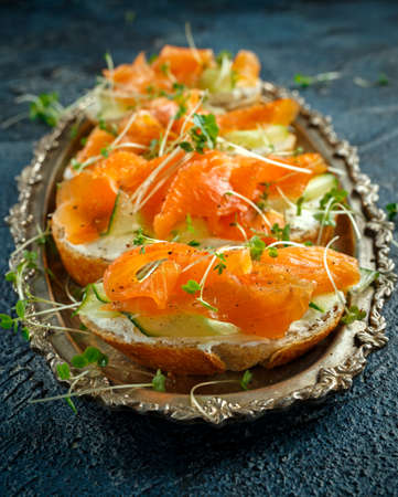 Smoked salmon bruschettas with soft cheese and cucumber shavings on a vitage plate