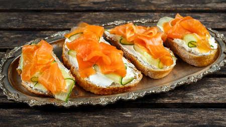 Sándwiches de salmón ahumado con queso blando y virutas de pepino en una placa de raclette Foto de archivo - 77624346
