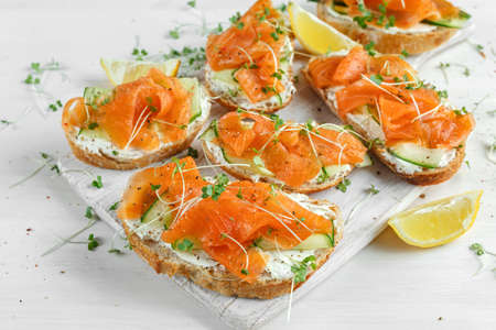Smoked salmon bruschettas with soft cheese and cucumber shavings on white board.