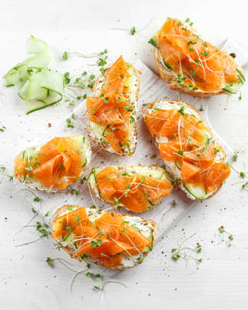 Sándwiches de salmón ahumado con queso blando y virutas de pescado en la tabla blanca . Foto de archivo - 77624347