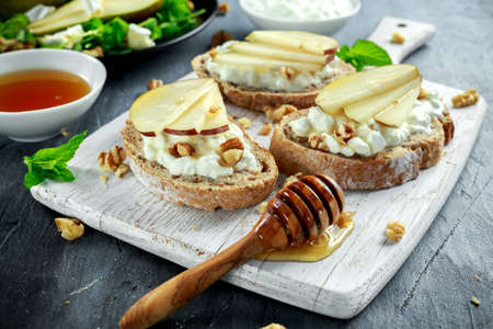 Fresh sweet Pears salad and bruschetta with cottage cheese, walnut on white board. Archivio Fotografico