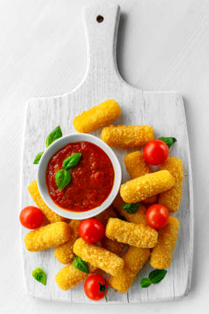 Breaded mozzarella cheese sticks with tomato basil sauce. Reklamní fotografie - 78594053