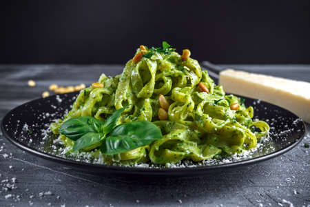 cooking oil: Tagliatelle pasta with pesto sauce, pine nuts and parmesan on black plate