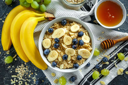 Bowl of Healthy Breakfast oatmeal with ripe blueberries, banana, honey, almonds and green grape. Top view