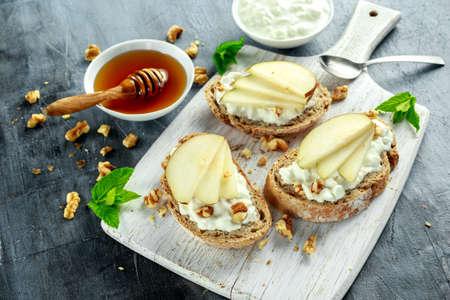 洋梨、蜂蜜、クルミとホワイト ボードにカッテージ チーズ前菜ブルスケッタ。 写真素材