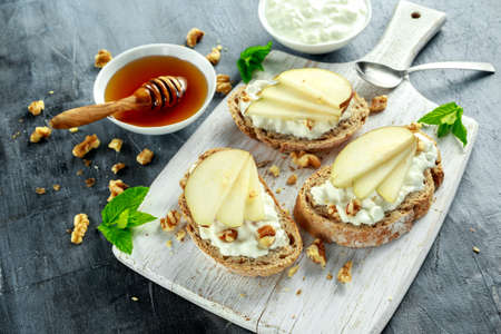 Appetizer bruschetta with pear, honey, walnut and cottage cheese on white board.
