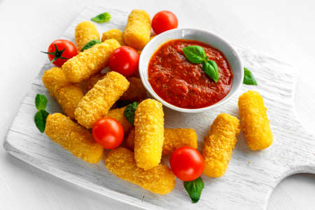 Breaded mozzarella cheese sticks with tomato basil sauce Stock Photo