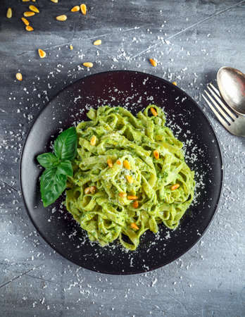 Tagliatelle pasta with pesto sauce, pine nuts and parmesan on black plate
