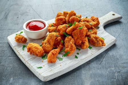 Nuggets de poulet croustillants frits avec du ketchup sur tableau blanc