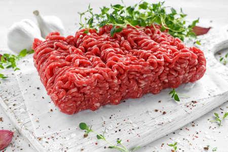 Viande hachée de boeuf cru frais avec du sel, du poivre, du piment et du thym frais sur le tableau blanc. Banque d'images - 79527011