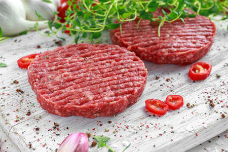 Fresh raw beef, round patties for making homemade burger on wooden white board