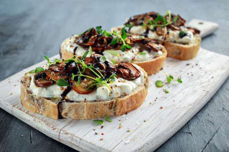 Garlic mushroom toast with creamy herbed ricotta chees spread Banque d'images