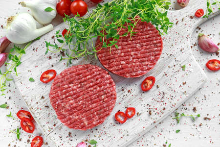 Fresh raw beef, round patties for making homemade burger on wooden white board Stock Photo - 79676554