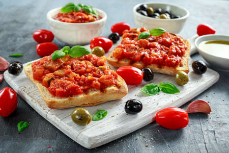 Fresh homemade crispy Italian appetizer Bruschetta topped with tomato, eggplant, Zucchini, Yellow pepper, garlic and basil on white wooden board. healthy food Stock Photo