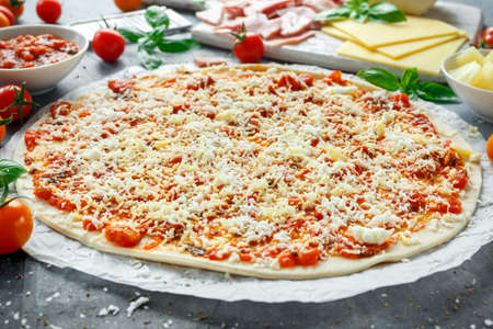 Ready to cook pizza with tomatoes sauce, cheese on Parchment paper. Stock Photo