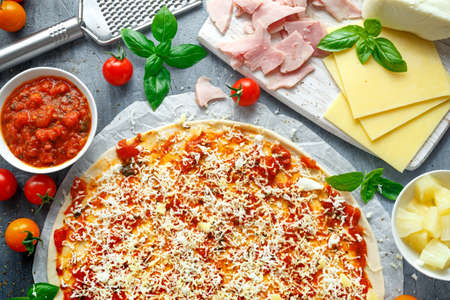 Ready to cook pizza with tomatoes sauce, cheese on Parchment paper. Stockfoto
