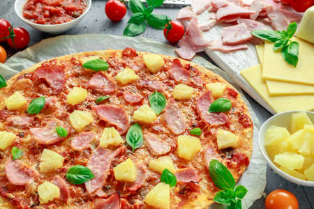 Fresh baked pizza hawaii with ham and pineapple, basil, tomatoes on backed paper. Stock Photo