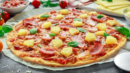 Fresh baked pizza hawaii with ham and pineapple, basil, tomatoes on backed paper Imagens