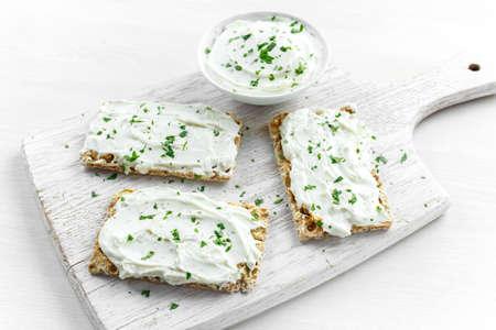 Eigengemaakte Knäckebroodstoost met Roomkaas en peterselie op witte houten raadsachtergrond. Stockfoto