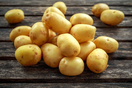raw baby new potatoes on rustic wooden background Stok Fotoğraf