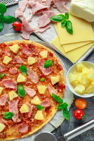 Fresh baked pizza hawaii with ham and pineapple, basil, tomatoes on backed paper Stock Photo